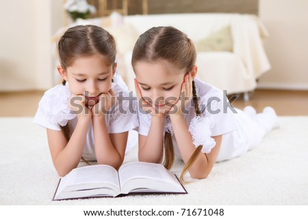 two twin sisters at home reading a book together, studying