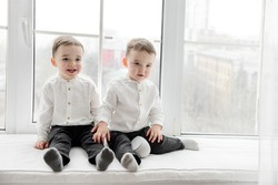 Two two-year-old twin boys in white shirts and black pants posing in front of the camera.