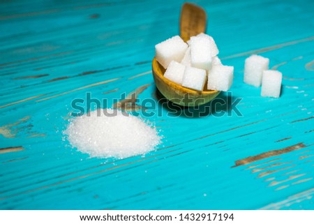 two types of sugar (refined sugar and granulated sugar) on a blue background with a wooden spoon