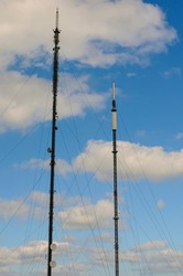 Two UK television and radio masts against a blue sky with clouds.