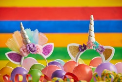 Two unicorn headbands in pile of multicolored balloons in front of brightly colored striped background