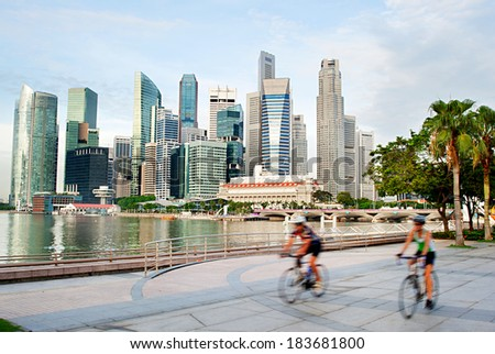 Two unidentified cyclists in Singapore. Singapore downtown on the background