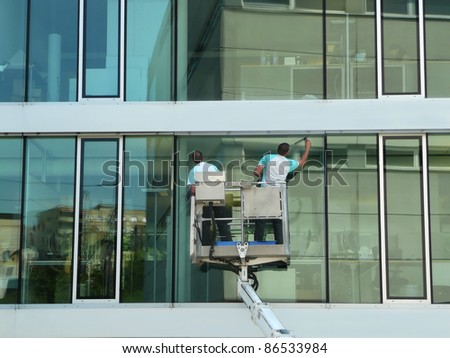 Two unidentified workers clean a modern office building