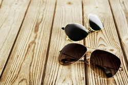 two unisex sunglasses close-up on a wooden background horizontal