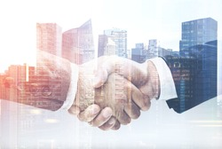Two unrecognizable businessmen shaking hands in a modern city. Partnership concept. Toned image double exposure