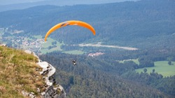 Two unrecognizable people are paragliding in tandem. Orange wing on a background of blue mountains. Mountain ridge between France and Switzerland. Summer sport and initiation. Masked people, COVID-19