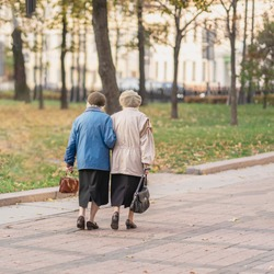 Two unrecognizable senior women walking together in the city, pensioners. Autumn, time, interests elderly, life style and friendship