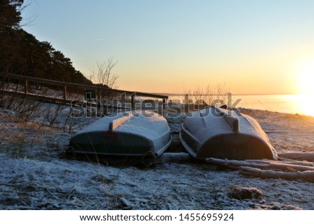 two upturned boats in the winter on the beach at sunset, Baltic sea, Latvia