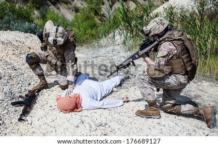 Two US marines making a search of killed muslim warrior