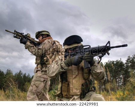 Two US Soldiers In Action Shooting The Enemy. HDR Image