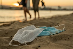 Two used disposable masks (protect from COVID-19, Coronavirus) are on a beach, covered with sand, leading to bad consequences like pollution or contamination of the nature and water