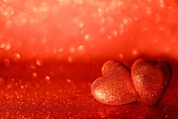 Two valentine hearts on red abstract background. Bright romantic card for sweethearts on happy anniversary, Valentine's Day, New Year, Christmas.  Selective focus with bokeh. Creative minimalism.