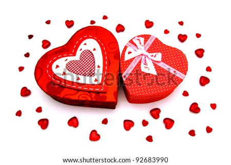 Two Valentines Day heart-shaped gift boxes with gems and confetti over white