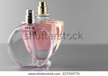 Two various bottles of woman perfume on gray background.