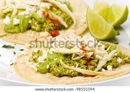 Two vegetarian green tofu chorizo tacos with a guacamole sauce and crumbly cheese.