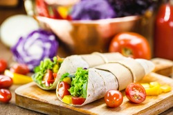 Two vegetarian tortilla wraps on wooden cutting board with vegetables in the background