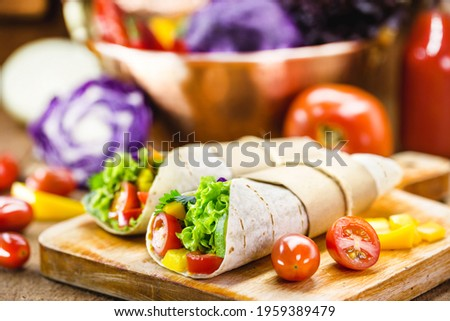 Two vegetarian tortilla wraps on wooden cutting board with vegetables in the background Foto stock ©