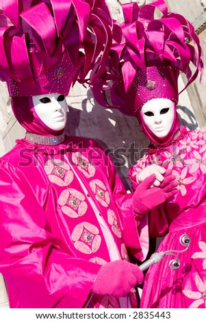 Two Venetians in pink costumes and white masks