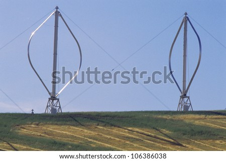 Two vertical-axis wind turbines standing on ground - stock photo