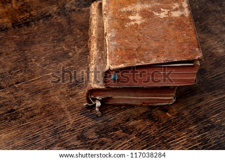 two very old books on a wooden table