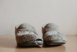 Two very worn, torn and widely used house slippers with a hole. Women's or girl's house slippers