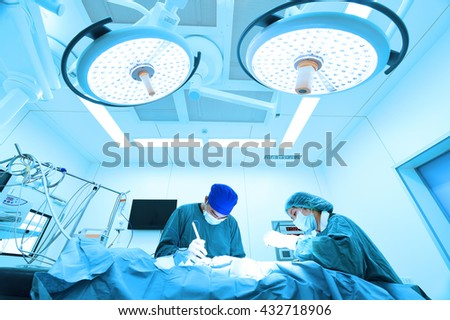 two veterinarian surgeons in operating room take with art lighting and blue filter