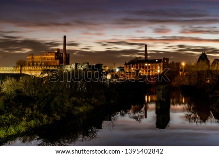 Two Victorian mills at dusk. Clouds at dusk and light reflected into the river.   #1395402842