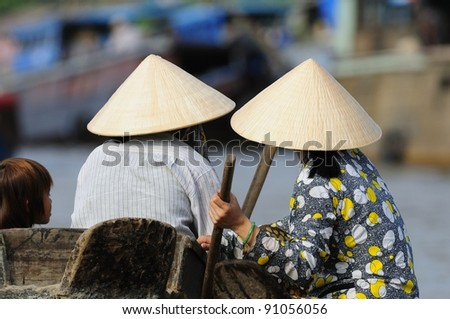 Two Vietnamese Seen at a Morning Floating Market in Vietnam.