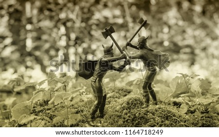 Two Vikings with double-sided axes fighting each other on a hill covered with moss and plants, vintage toy soldiers, blurry background, Old Norse myths, norsemen theme, bi-color style image