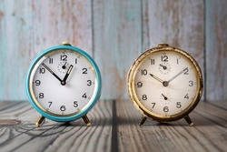Two vintage alarm clocks on a wooden background