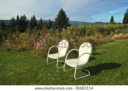 Two vintage chairs face a valley view from a hilltop farm