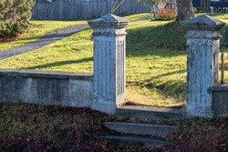 Two vintage concrete gate posts without the gate. There are three steps leading up to the posts. A concrete fence is on both sides of the posts. There is green grass, trees and a wooden fence behind.