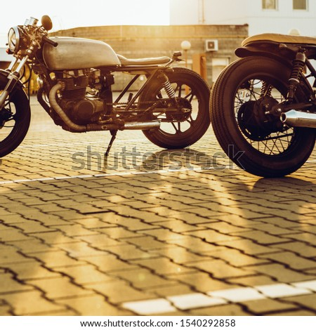 Two vintage custom motorbike cafe racers motorcycle looking in opposite directions on empty rooftop parking lot with backlight sun during sunset. Confrontation of urban styles. Hipster lifestyle. #1540292858