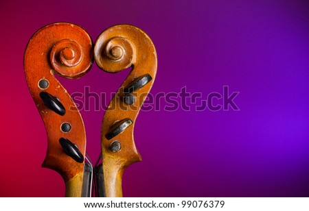Two vintage violin scrolls make heart shape with copy-space