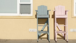 Two vintage wooden lifeguard chairs by yellow wall, California USA. Empty life guard retro high seat by ocean sea beach. Minimal simple trendy pop atmosphere, summertime aesthetic. Los Angeles vibes.