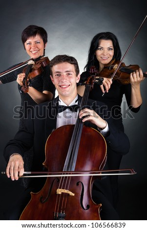 Two violinist and cellist played on a dark background