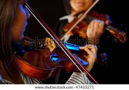 two violinists playing violins on a black background