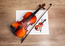 two violins and a music book on a wooden table, top view