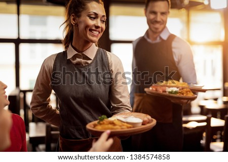 Two waiters serving lunch and brining food to their gusts in a tavern. Focus is on happy waitress.