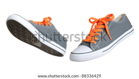 Two walking grey sneakers isolated on white background