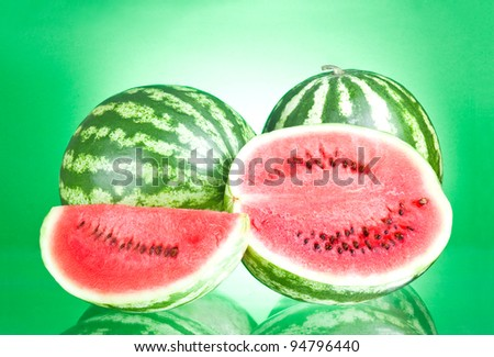 Two watermelon, half and Slice on a green background