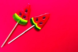 Two watermelon-shaped lollipops on a bright red background. Copy space