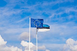 Two waving flags of European Union and Estonia against blue sky. Estonian independence day is celebrated on February 24. Eesti Vabariigi aastapäev