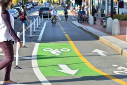 Two-way protected bike lanes with pavement markers, striped median, buffer zone and flexible delineators in city street
