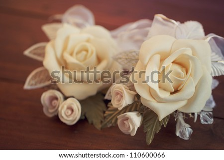 Two wedding boutonnieres of roses lie on the board