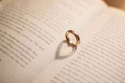 Two wedding Ring on the bible with shadow of heart shape on the open page. Engagement, wedding and nuptials. Marriage. A vow of love.