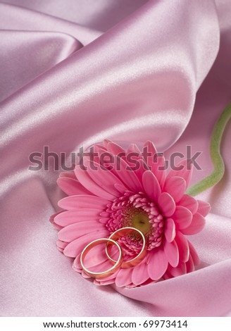 Two wedding rings and flowers lie on bed silk