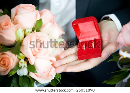 two wedding rings and rose bouquet