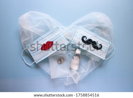 Two wedding rings, antiseptic and protective face masks with a mustache and lips painted on them are on blue background. The concept of wedding ceremonies during a pandemic of coronavirus COVID-19