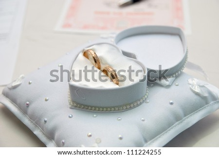 Two wedding rings in a heart-shaped box